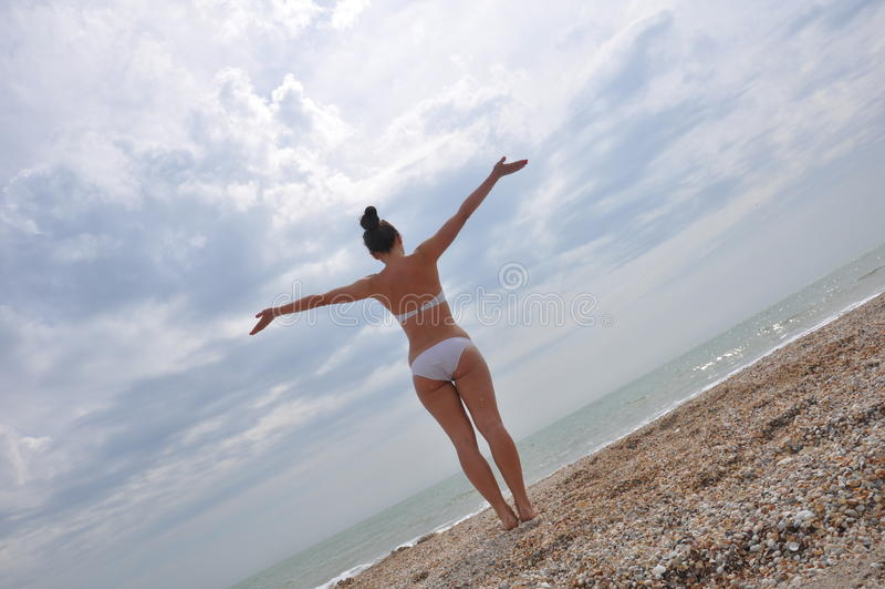 Chica joven en un bikini que mira el mar foto de archivo