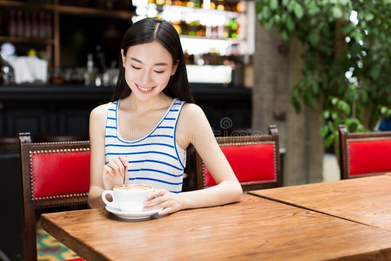 Chica joven en un café de consumición del café foto de archivo libre de regalías