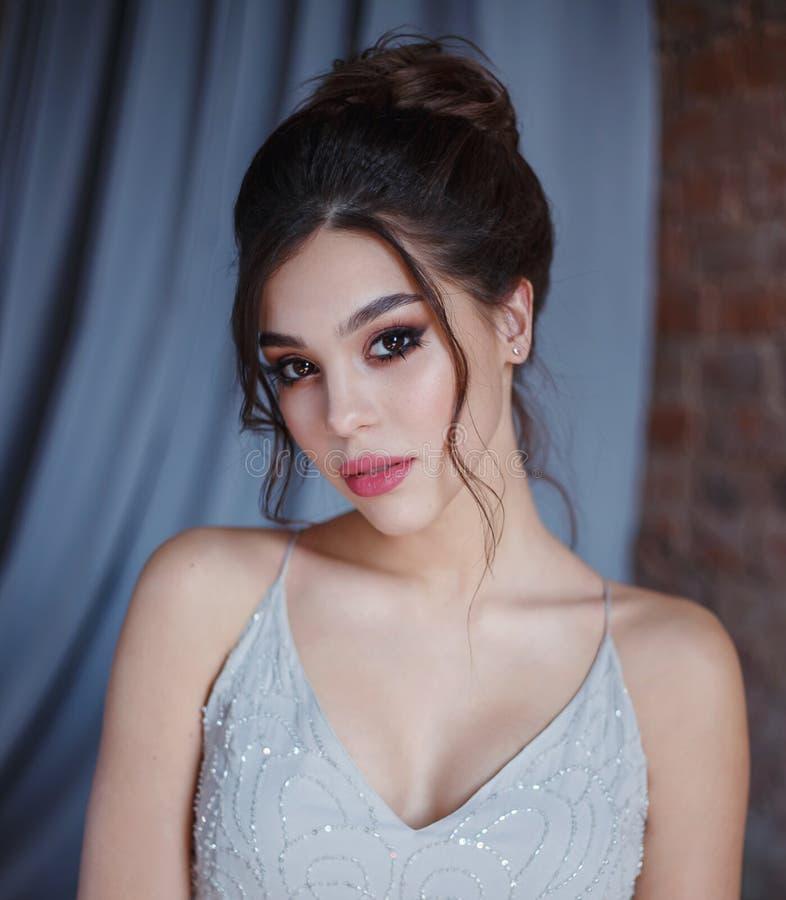 Chica joven en un gris, vestido de noche que presenta en la cámara Maquillaje brillante de la tarde con las pestañas largas y los imagenes de archivo