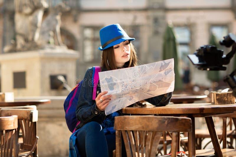 Chica joven en un sombrero azul que descansa sobre la terraza del verano en la ciudad vieja, y mirando el mapa Lviv, Ucrania imagen de archivo
