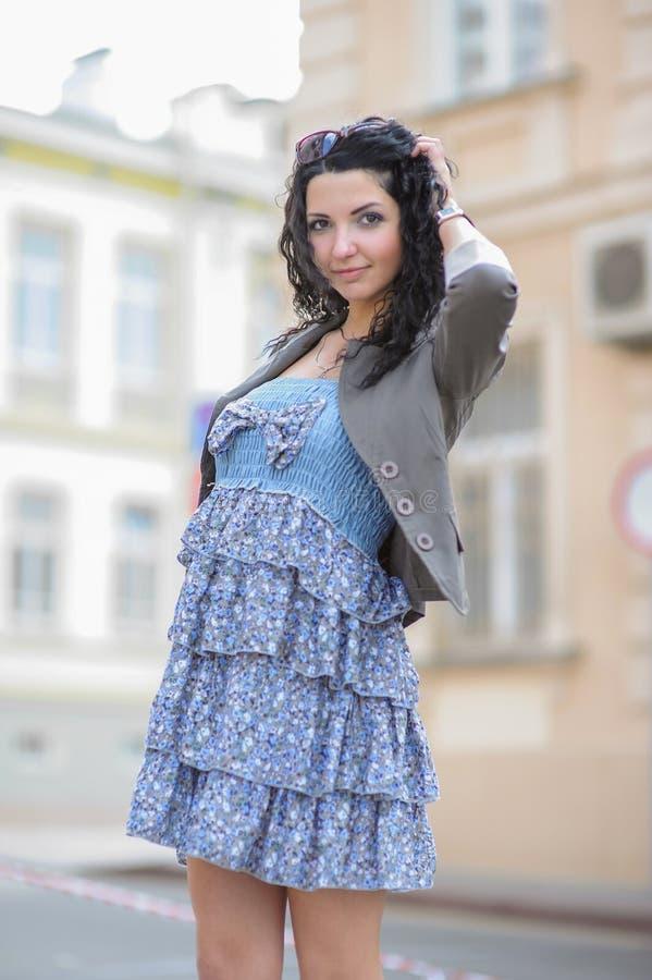 Chica joven en un vestido azul que camina en la ciudad Mujer joven que presenta en un vestido azul en la ciudad vieja imagen de archivo