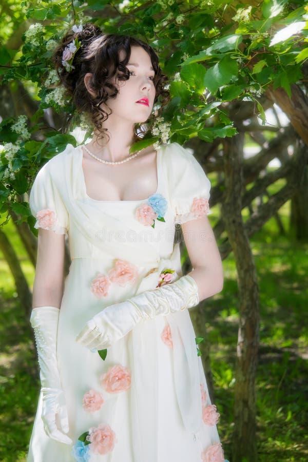 Chica joven en un vestido blanco largo elegante de la novia en flores fotografía de archivo