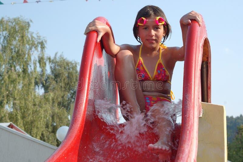 Chica joven en una diapositiva de la piscina foto de archivo