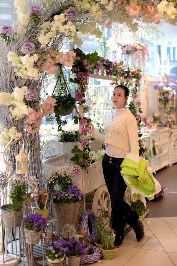 Chica joven en una floristería imagen de archivo