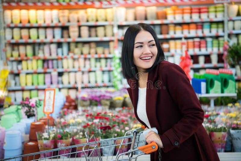 Chica joven en una floristería que sonríe y que empuja el carro de la compra fotografía de archivo libre de regalías