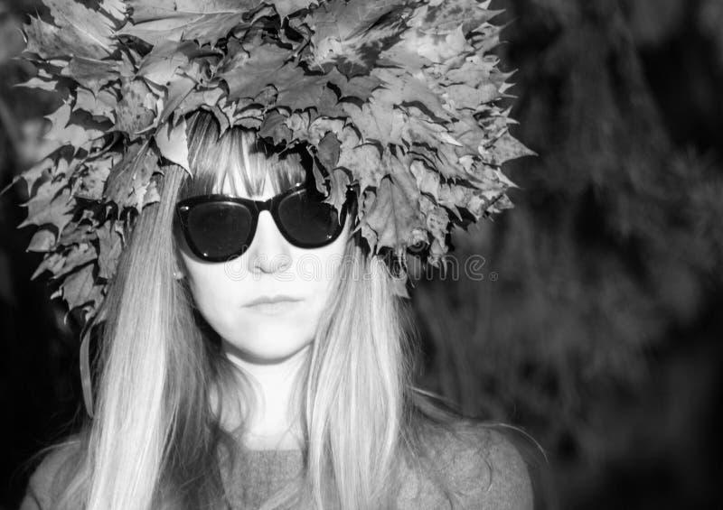 Chica joven en una guirnalda de hojas La muchacha en el parque Otoño foto de archivo
