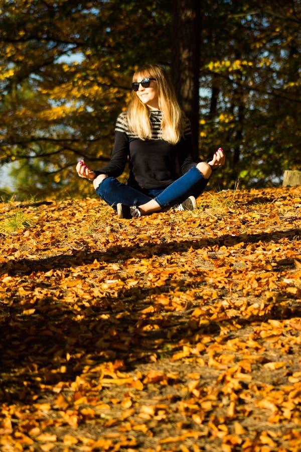 Chica joven en una guirnalda de hojas La muchacha en el parque Otoño fotografía de archivo
