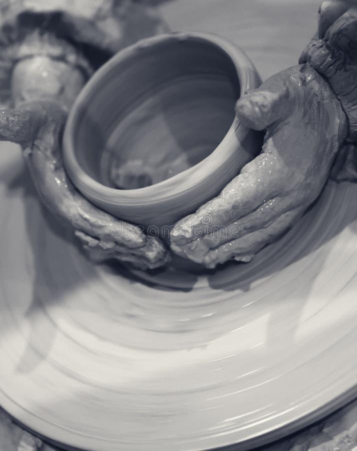 Chica joven en vías de la fabricación del cuenco de la arcilla en la rueda de la cerámica fotos de archivo