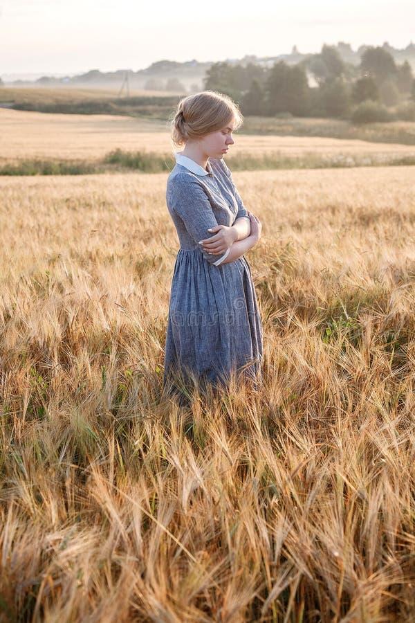 Chica joven en vestido azul con miradas recogidas del pelo cuidadosamente en el campo de oídos en la salida del sol Amanecer de n imagen de archivo libre de regalías