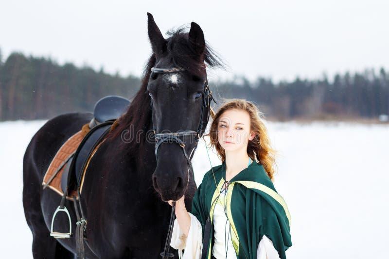 Chica joven en vestido con el caballo negro en invierno imágenes de archivo libres de regalías