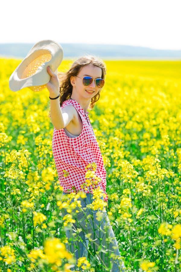 Chica joven en vestido a cuadros rojo y sunhat que presenta en campo de la violaci?n de semilla oleaginosa imagen de archivo libre de regalías