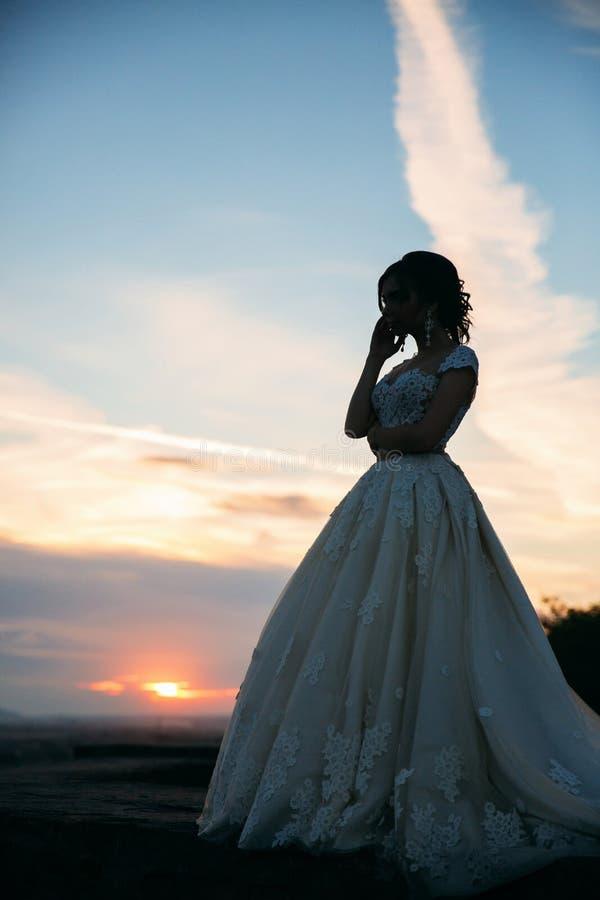 Chica joven en vestido de boda en el parque que presenta para el fotógrafo Tiempo soleado, verano imágenes de archivo libres de regalías