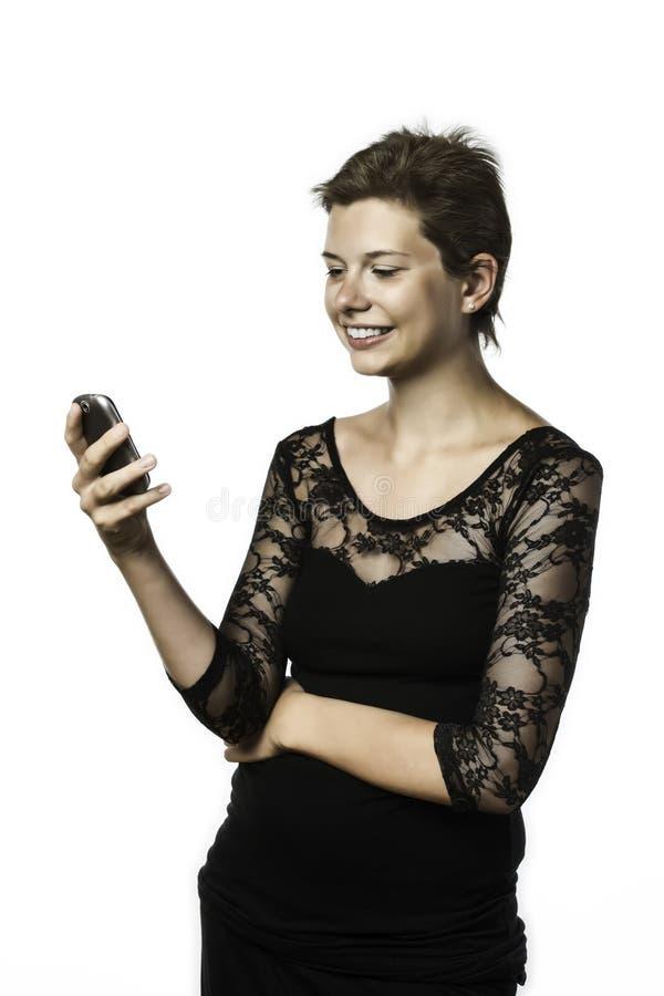 Chica joven en vestido negro que escribe un mensaje corto imagenes de archivo