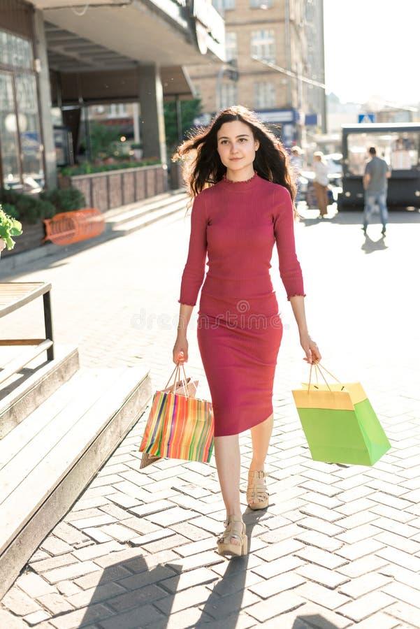 Chica joven en vestido rojo con los bolsos de compras en la calle foto de archivo libre de regalías