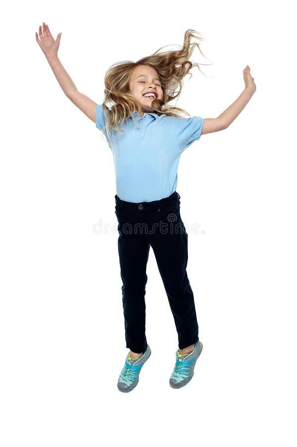 Chica joven encantada que salta arriba en el aire fotografía de archivo libre de regalías