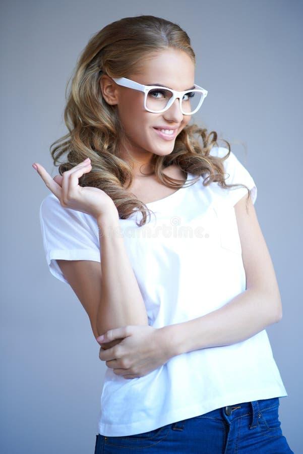 Chica joven encantadora que desgasta los vidrios blancos con estilo foto de archivo libre de regalías