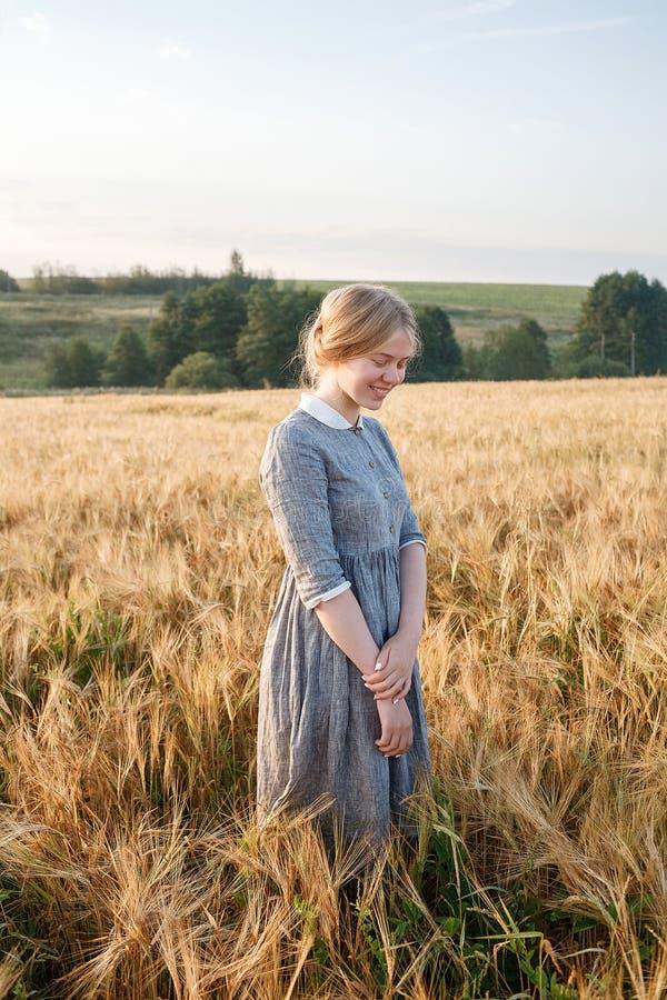 Chica joven feliz agradable en vestido al aire libre pasado de moda azul en el campo de oro de oídos en el amanecer Boscaje verde imagenes de archivo