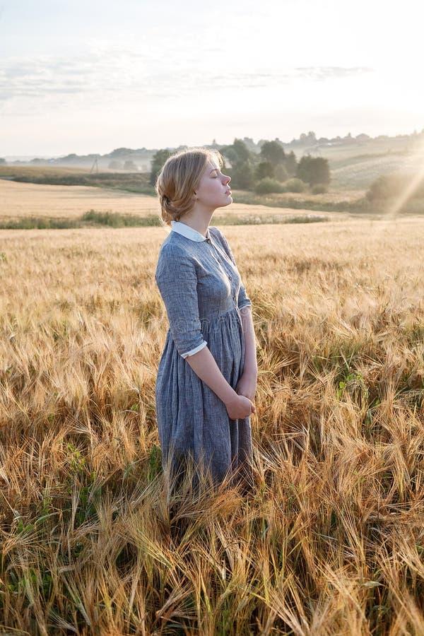 Chica joven feliz agradable en vestido al aire libre pasado de moda azul en el campo de oro de oídos en la salida del sol Amanece fotos de archivo