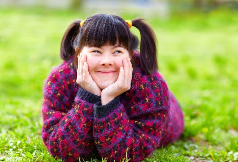 Chica joven feliz con incapacidad en césped de la primavera fotos de archivo
