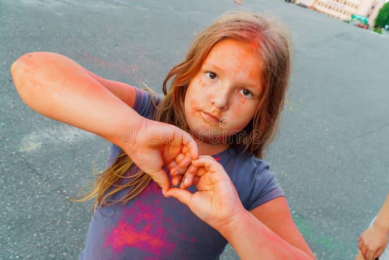 Chica joven feliz cubierta con la pintura seca colorida en el festival de Holi fotografía de archivo