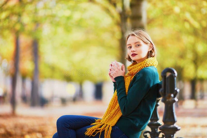Chica joven feliz en bufanda amarilla que camina en parque del otoño imagen de archivo