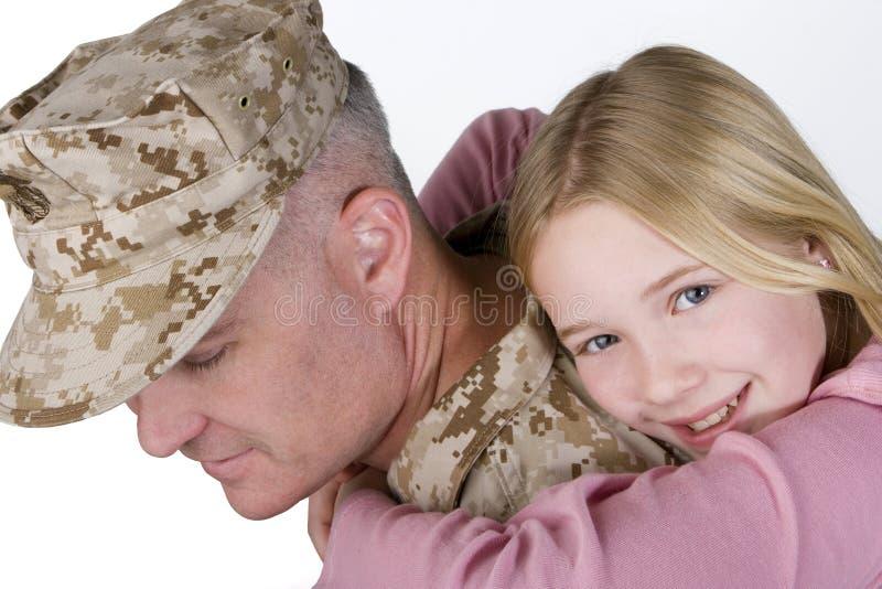 Chica joven feliz que abraza a su padre en uniforme fotografía de archivo libre de regalías