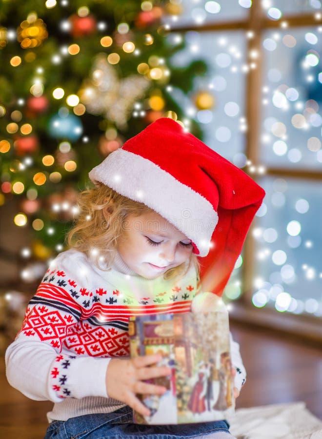 Chica joven feliz que abre un rectángulo de regalo imagen de archivo libre de regalías