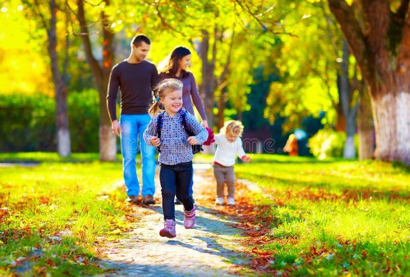 Chica joven feliz que corre en parque del otoño con su familia en fondo imagen de archivo