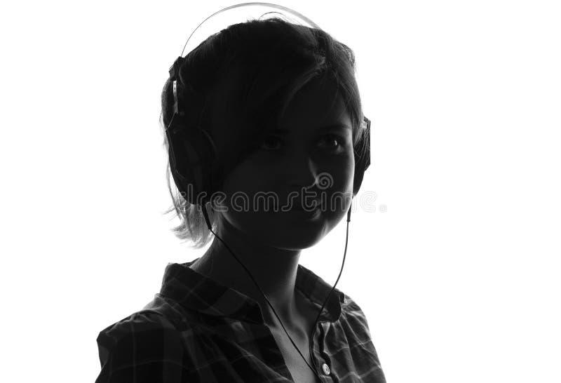 Chica joven feliz que escucha la música en los auriculares fotos de archivo libres de regalías