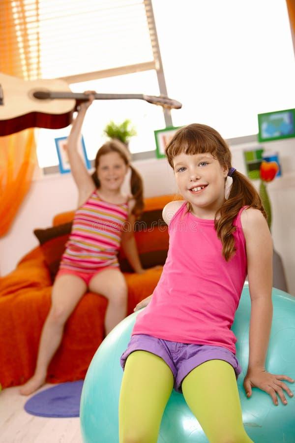 Chica joven feliz que se sienta en bola de la gimnasia foto de archivo libre de regalías