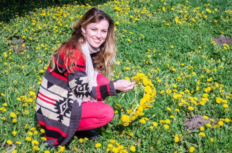Chica joven feliz que se sienta en el parque en un campo de la hierba y de los dientes de león y que escoge las flores para hacer foto de archivo libre de regalías