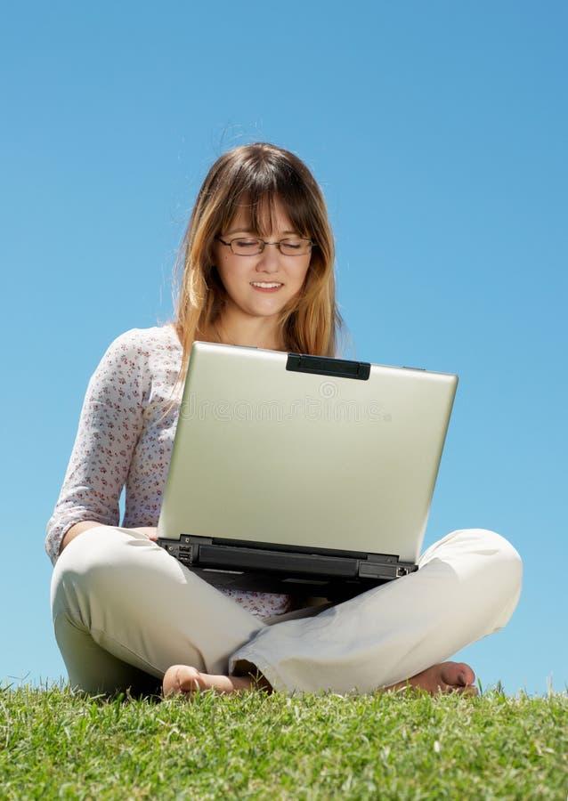 Chica joven feliz que sonríe y que trabaja en una computadora portátil imagen de archivo