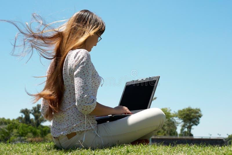 Chica joven feliz que sonríe y que trabaja en una computadora portátil fotografía de archivo libre de regalías