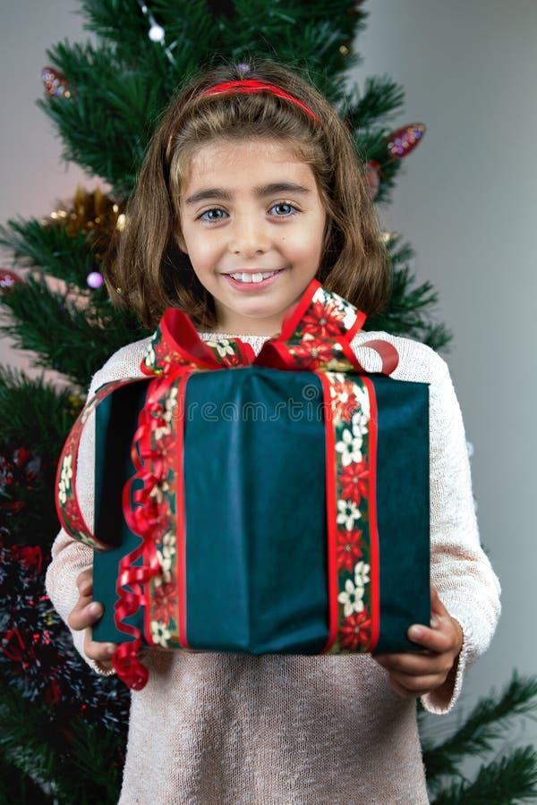 Chica joven feliz que sostiene la caja del regalo de Navidad en frente un Cristo foto de archivo