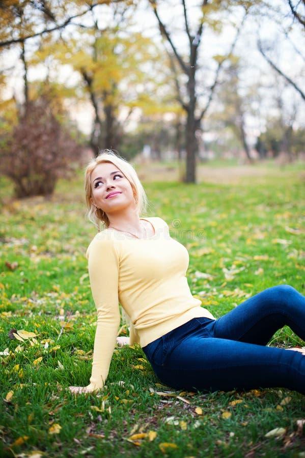 Chica joven feliz sonriente que sienta al aire libre la mirada fotos de archivo