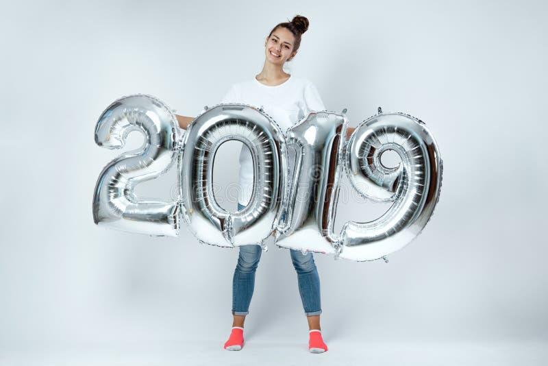 Chica joven feliz vestida en la camiseta blanca, los vaqueros y los calcetines rosados sosteniendo los globos en la forma de los  imagenes de archivo