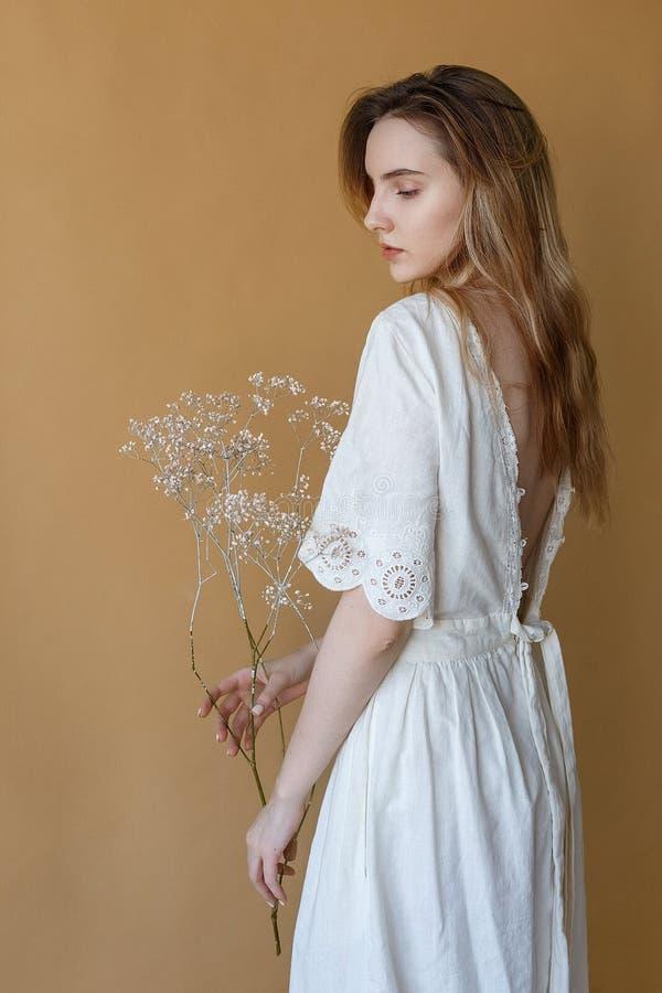 Chica joven flaca hermosa con el pelo largo en el vestido blanco en el fondo beige que sostiene las flores blancas en sus manos imágenes de archivo libres de regalías