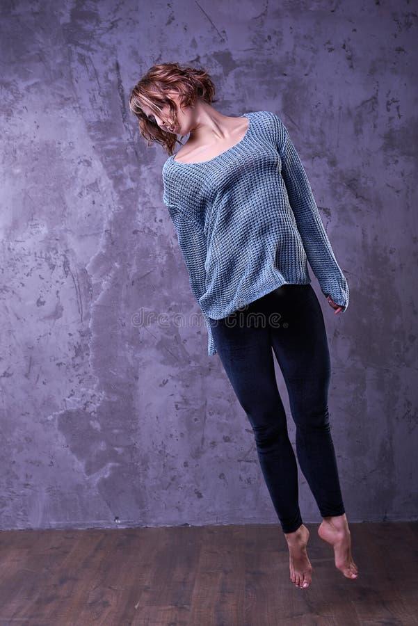 Chica joven hermosa, bailarín profesional, presentando en un salto en el estudio foto de archivo libre de regalías