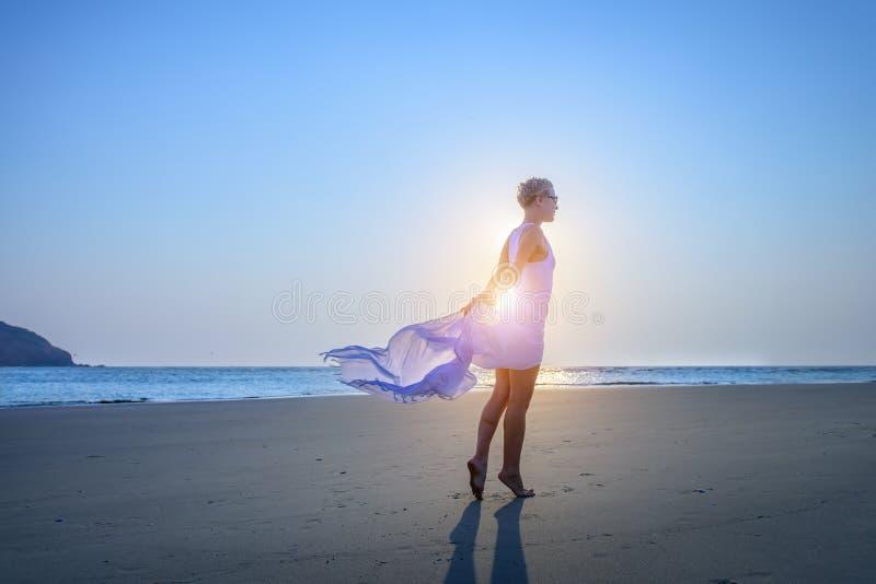 Chica joven hermosa con el pelo corto en un vestido blanco largo en la playa arenosa por el mar durante puesta del sol Luz contra imagenes de archivo