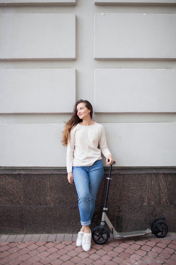 Chica joven hermosa con el pelo marrón largo parado mientras que monta la vespa en el fondo de la pared gris La visten en a fotografía de archivo
