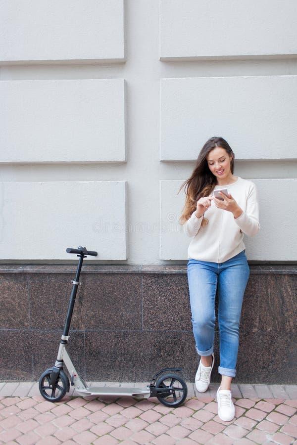 Chica joven hermosa con el pelo marrón largo parado mientras que monta la vespa, para escribir a un amigo en el teléfono en el fo fotos de archivo libres de regalías