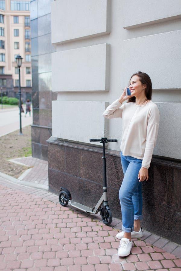 Chica joven hermosa con el pelo marrón largo parado mientras que monta la vespa, para llamar a un amigo en el teléfono en el fond imágenes de archivo libres de regalías