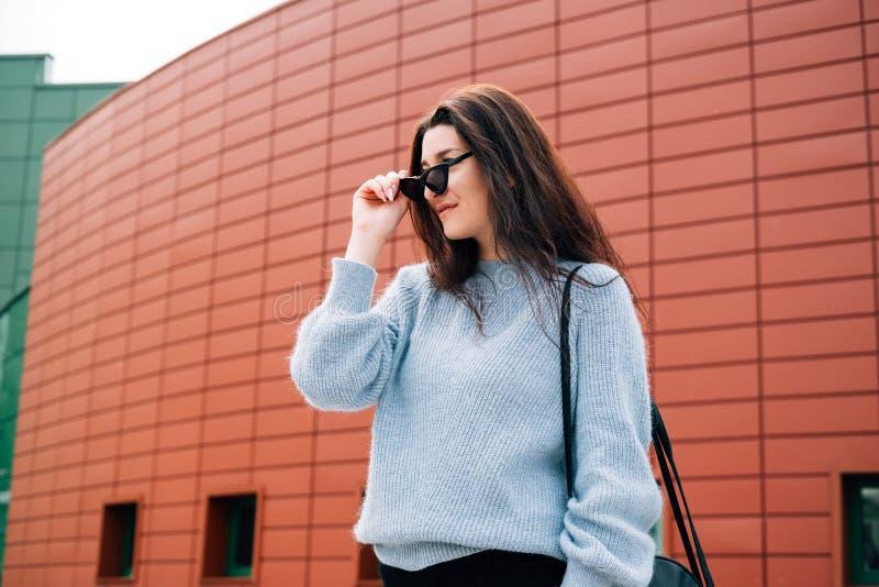 Chica joven hermosa con el pelo oscuro que lleva la ropa casual que presenta cerca de la pared roja, estilo de la calle, retrato  fotografía de archivo libre de regalías