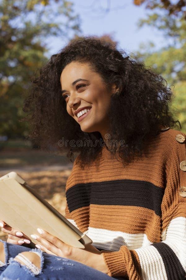Chica joven hermosa con el pelo rizado oscuro usando la tableta, al aire libre foto de archivo libre de regalías