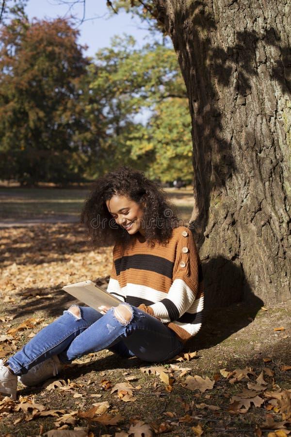Chica joven hermosa con el pelo rizado oscuro usando la tableta, al aire libre imagenes de archivo