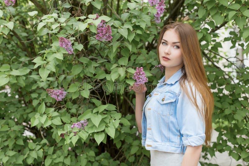 Chica joven hermosa con el pelo rojo en el jardín con la lila fotografía de archivo