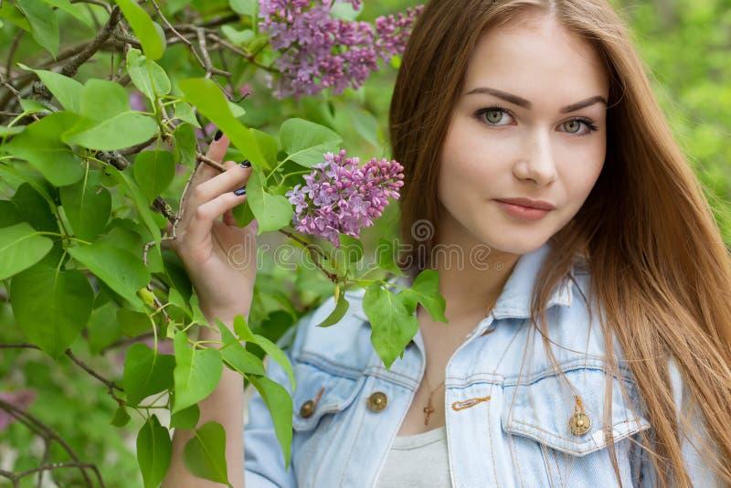 Chica joven hermosa con el pelo rojo en el jardín con la lila imagenes de archivo