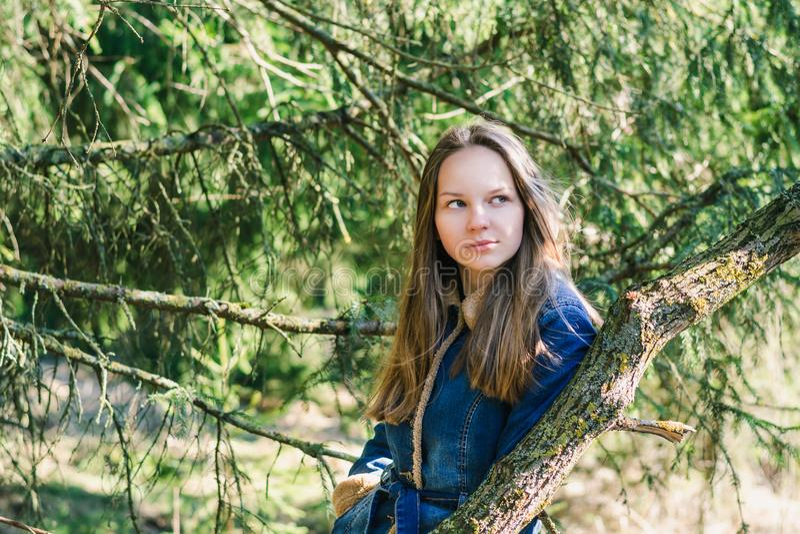 Chica joven hermosa con el pelo rubio largo en una chaqueta azul del dril de algod?n en un bosque verde en un d?a de primavera so imágenes de archivo libres de regalías