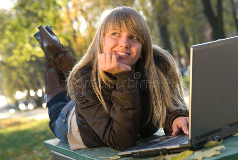 Chica joven hermosa con la computadora portátil imagenes de archivo