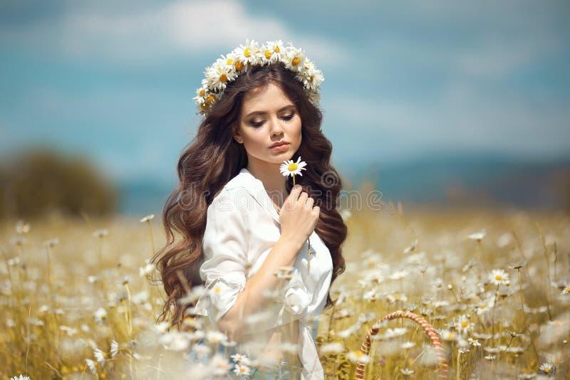 Chica joven hermosa con la flor que goza en campo de la manzanilla Mujer morena feliz despreocupada con la guirnalda en el pelo o imagen de archivo